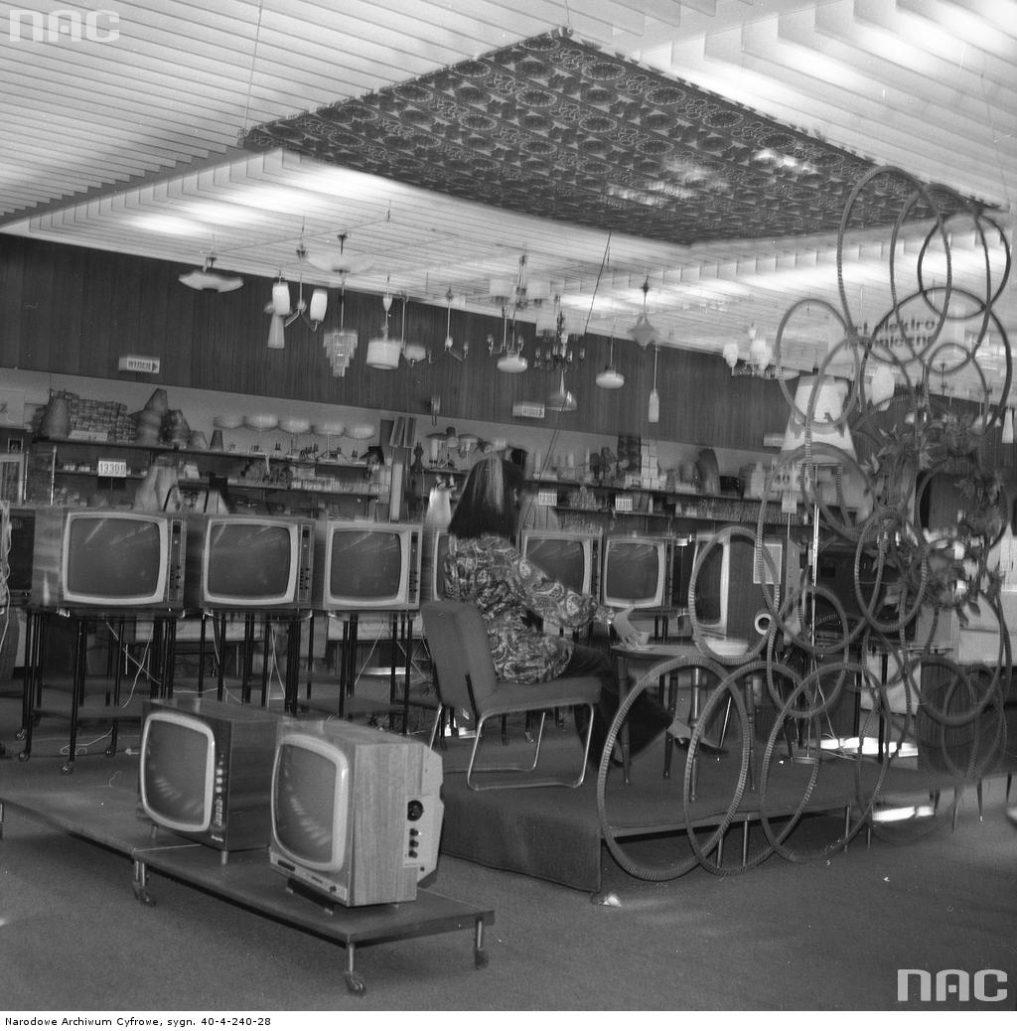 """Wnętrze sali sprzedaży """"Sezamu"""" w końcu 1969 r. Na zdjęciu stoisko z telewizorami. Pośrodku Tosca Lux, obok Fregata, w głębi na regałach widać Granit 101. Zdjęcie Grażyny Rutowskiej. Zbiory Narodowego Archiwum Cyfrowego"""