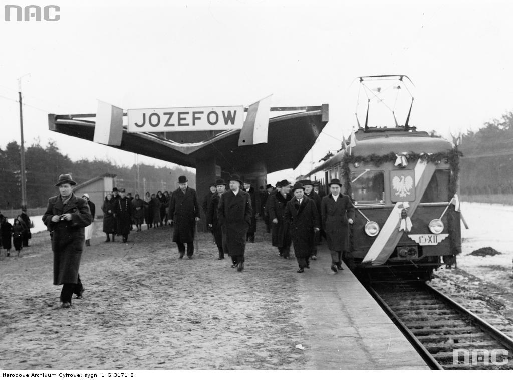 Otwarcie stacji w Józefowie na linii otwockiej 15 grudnia 1936 r. Na peronie drugi z lewej minister komunikacji Janusz Ulrych. Widoczny skład elektryczny E-91. Fot. Narodowe Archiwum Cyfrowe
