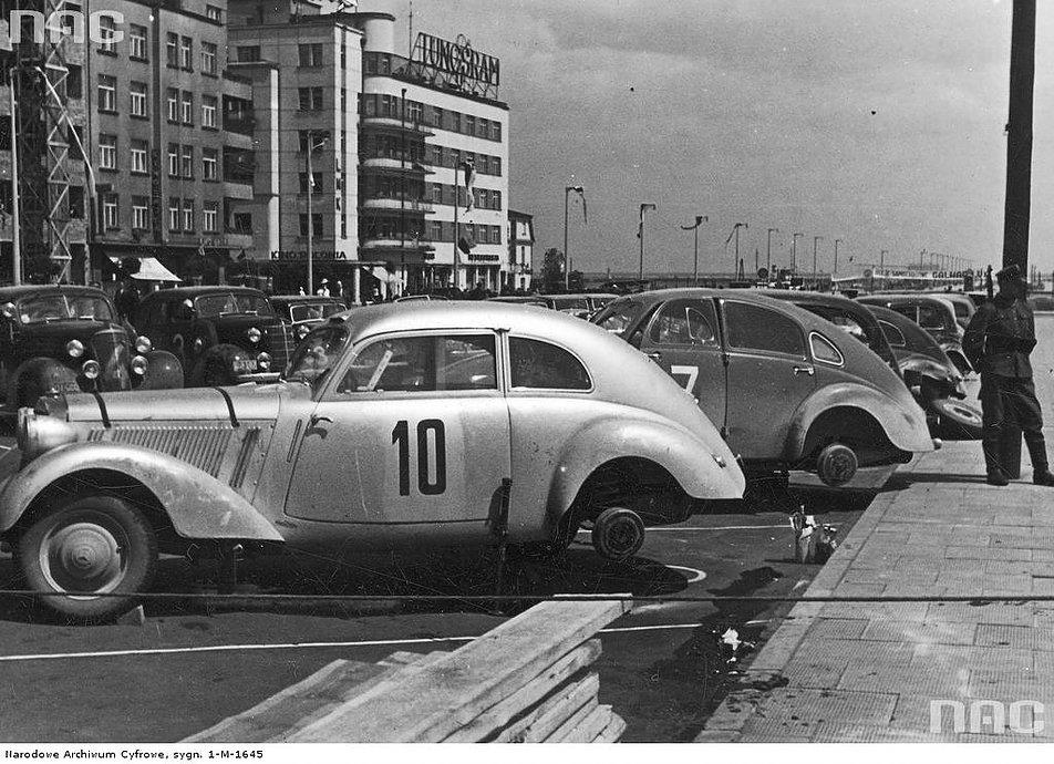 To samo miejsce w trakcie rajdu samochodowego w 1938 r. Na dachu kamienicy Pręgowskiego widnieje neon firmy Tungsram. Zwracają uwagę opływowe karoserie samochodów. Fotografia ze zbioru Narodowego Archiwum Cyfrowego