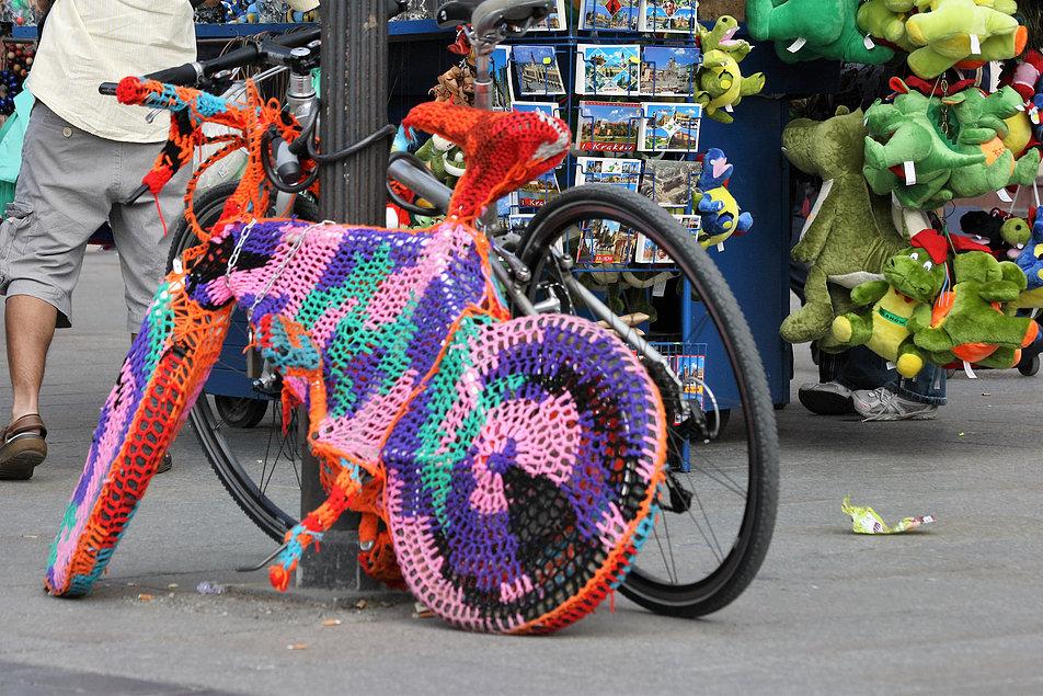 Włóczkowy rower na Rynku Głównym w Krakowie. Obok wystawione na sprzedaż zielone wawelskie smoki. Fot. Jerzy S. Majewski