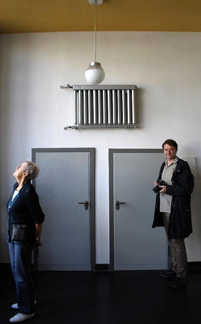 Dessau, Bauhaus. Na klatce schodowej szkoły kaloryfer nad drzwiami pełni dodatkowo funkcję tradycyjnego obrazu. Z prawej architekt Krzysztof Mycielski. Fot. Jerzy S. Majewski