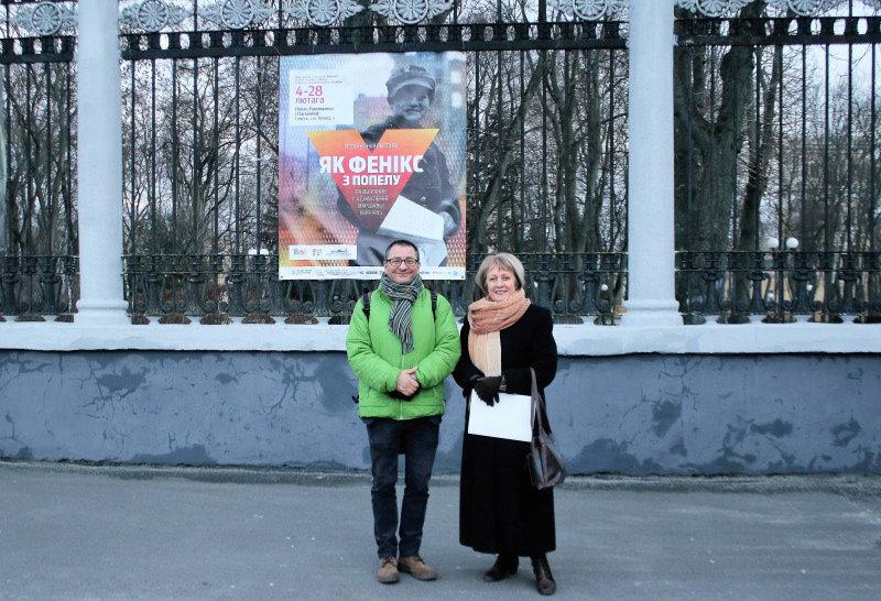 """Tatiana Litwinowa i autor tekstu przed ogrodzeniem parku w Homlu. W tle widać plakat wystawy """"Jak Feniks z popiołu."""" Fot. Aleksander Matiuszonek"""