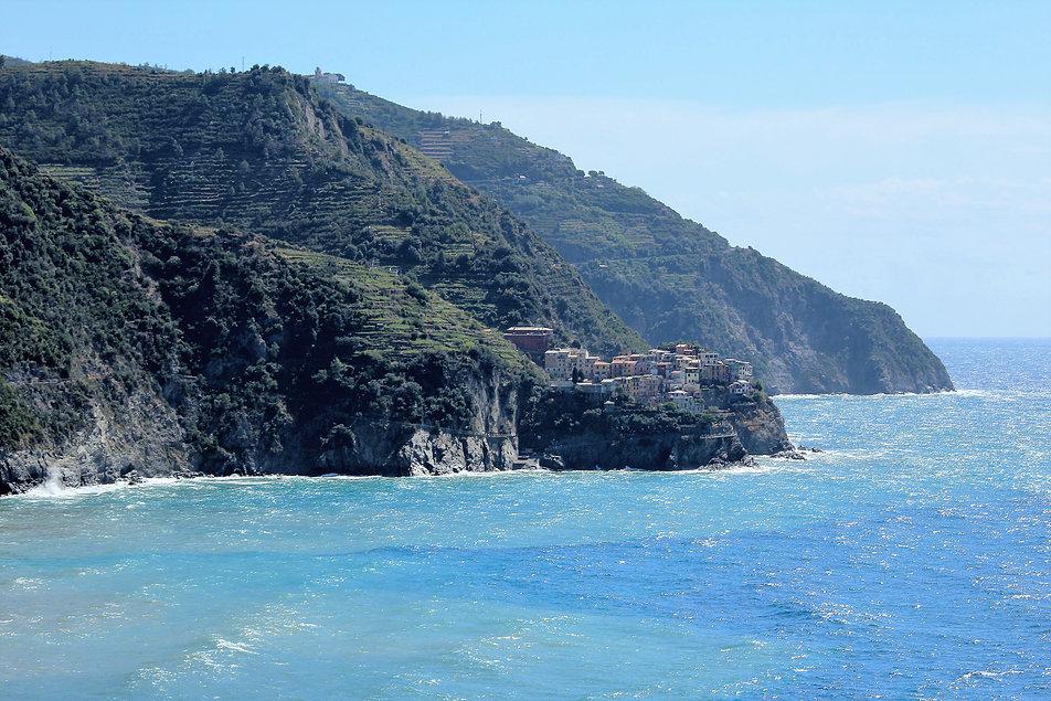 Położona na skale Manarola widziana od zachodu. W głębi za górą znajduje się Riomaggiore. Na zboczach widać tarasowo ukształtowane winnice. Fot. Jerzy S. Majewski