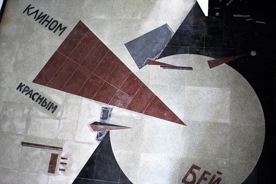 """Witebsk. Ul. Chagalla. Współczesna posadzka w dawnym budynku Ludowej Szkoły Sztuk Pięknych jest kopią plakatu propagandowego El. Lissitzkiego """"Czerwonym klinem bij białych z 1919 r. Kompozycja, która przeszła do wszystkich podręczników konstruktywizmu powstała w czasie gdy autor pracował w Witebsku. Fot. Jerzy S. Majewski"""